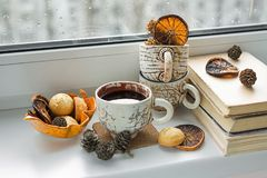 Autumn mood card. Black coffee on the window at rainy weather. B. Some old books, a cup of black coffee. Rainy day. Dried orange and cones stock photos