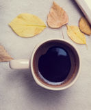 Autumn mood. Cup of coffee and leaves. Toned photo Stock Images