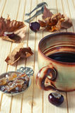 Autumn mood: fallen leaves, chestnuts and huge mug of coffee. Autumn still life: fallen leaves, chestnuts and  large cup of coffee Stock Photos