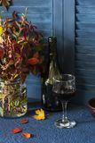 Autumn mood still life with a bouquet of autumn leaves and a glass of red wine stock photo