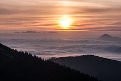 Autumn morning Carpathian mountains panorama with colorful sky, sun, misty and only few highest hills and mountain ranges above Stock Images