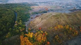 Autumn morning nature. aeriel video footage. Hill with road and colorful trees. Village on background. Cold colors of. Fog. Aerial video footage. Countruside stock video footage