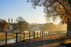 Autumn morning on old town embankment filled with light. Embankment of the old town strewn with foliage and filled with light on autumn morning Stock Photos