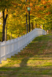 Autumn Morning white picket fence. Scenic autumn morning with leaves changing colors and diminishing perspective white picket fence in Port Gamble Washington Stock Image