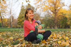 Autumn mother baby. Mother hugging baby in autumn nature Stock Image