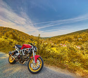 Autumn Motorbike Mountain Landscape. Red motorbike on country road landscape in autumn Royalty Free Stock Photo