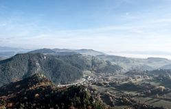 Autumn mountain countryside with hills, meadows, colorful forest, blue sky with mist in valleys in Slovakia. View from Hricovsky hrad castle riuins Stock Image