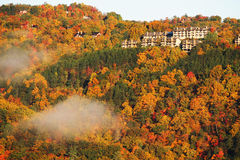 Autumn mountain forest in morning sunlight with cloud and hotel buildings Stock Images