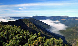 Autumn mountain panorama with misty and blue sky Stock Images