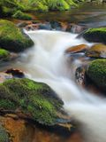 Autumn mountain river with blurred waves, water is running between mossy boulders and bubbles create trails on level. Royalty Free Stock Photos