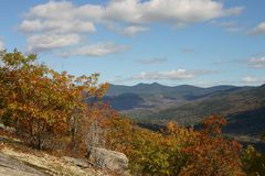 Autumn mountain scene. A beautiful view from the top of the mountain with fall foliage and mountain ranges Stock Image