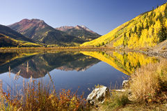 Autumn Mountain Vista. Rocky Mountain foliage reflects in a clear mountain lake royalty free stock image