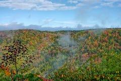 Autumn mountainns as fog lifts. Beautiful colors of the autumn season against a blue sky and clouds as fog rolls and lifts above the mountains Stock Photos