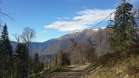 Autumn in the mountains, snow-capped peaks and clouds. Autumn in the mountains of Krasnaya Polyana, the cable car, snow-capped peaks and clouds Stock Photography