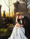 Autumn mourning. Young Victorian widow mourning on a tombstone at Halloween Royalty Free Stock Photography