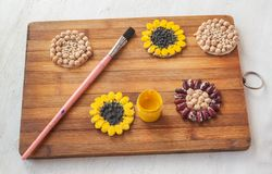 Autumn natural  materials for children`s creativity. Natural materials for children`s creativity. Flower of the pumpkin seeds and chickpeas on a circle of paper Stock Photos