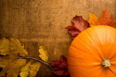 Autumn nature morte with orange pumpkin. Autumn scene with pumpkin and colourful leaves on wooden table Royalty Free Stock Photos