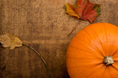 AUTUMN NATURE MORTE WITH ORANGE PUMPKIN. Autumn scene with pumpkin and colourful leaves on wooden table Stock Images
