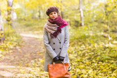 Autumn, nature, people concept - beautiful young woman in a grey coat and a beret standing in the park. royalty free stock images