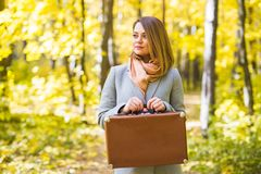 Autumn, nature and people concept - Portrait of beautiful smiling woman with brown suitcase in autumn nature royalty free stock images