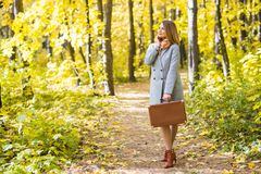 Autumn, nature and people concept - Young beautiful woman in grey coat in fall nature stock photos