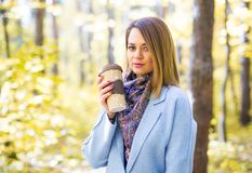 Autumn, nature, people concept - young brunette woman in a blue coat standing in the park with a cup of coffee royalty free stock photo