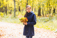 Autumn, nature and people concept - Young girl in park with bouquet of leaves.  Stock Images