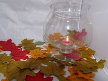 Autumn night light. A large glass with a flickering candle inside set among colourful autumn leaves Stock Images
