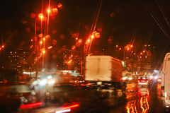 Autumn Night Rain Windshield City Road Cars Lights. View through car windshield to night road with moving cars. Autumn, rain, reflections Royalty Free Stock Photo