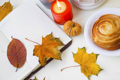 Autumn notebook with dried leaves, candle and honey roll bun Royalty Free Stock Images