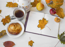 Autumn notebook with dried leaves, tea cup,candle lantern,and ho Royalty Free Stock Photography