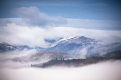 Autumn, November foggy and snowy morning mountain panorama. Stock Images
