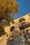Autumn in the old city. Yellow tree casts a shadow on the old house facade Royalty Free Stock Photo