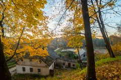 Old  houses in nature fall. Autumn and old houses in forest, Lithuania royalty free stock photo