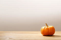 Autumn orange small pumpkin. On wooden table royalty free stock photography