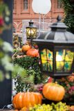 Autumn outdoor decorations at the festival. Orange pumpkin and retro forged lanterns with maple leaves,flowers royalty free stock images