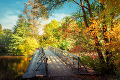 Autumn in outdoor park with wooden bridge on lake Royalty Free Stock Images