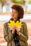 Autumn outdoor portrait of beautiful African American young woman holding yellow leaves - Black people royalty free stock photos