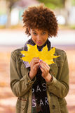 Autumn outdoor portrait of beautiful African American young woman holding yellow leaves - Black people royalty free stock image