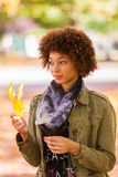 Autumn outdoor portrait of beautiful African American young woman holding yellow leaves - Black people stock photo