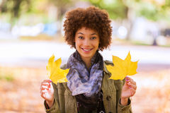 Autumn outdoor portrait of beautiful African American young woman holding yellow leaves - Black people stock photography