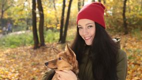 Portrait of smiling woman with her dog in autumn stock footage