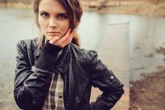 Autumn outdoor portrait of young beautiful woman with natural makeup in leather jacket and plaid shirt Stock Image