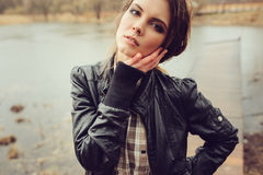 Autumn outdoor portrait of young beautiful woman with natural makeup in leather jacket and plaid shirt Royalty Free Stock Image