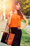 Autumn outfit color.Sophisticated brunette woman wearing elegant orange shirt black skirt and holding colorful leather bag. Outdoor fashion shot Royalty Free Stock Photos