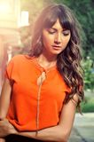 Autumn outfit color .Sophisticated brunette woman wearing elegant orange shirt with golden necklace. Outdoor fashion shot Royalty Free Stock Image
