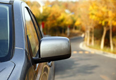 Autumn outing. Close-up of the car is driving on autumn's road Stock Photography