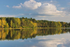 Autumn over the water. The photo shows a water reservoir. Its shores are covered with deciduous trees. It is autumn, some leaves took on a yellow and brown Stock Photo