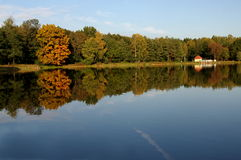 Autumn over the water. The photo shows a water reservoir. Its shores are covered with deciduous trees. It is autumn, some leaves took on a yellow and brown Stock Image