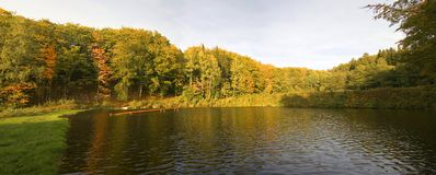 Autumn panorama. Panorama of autumn trees behind a pond Royalty Free Stock Photo